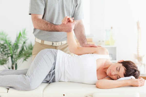 Chiropractor manipulating a woman's arm